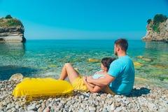 Paarzitting op rotsachtig strand die op zee kijken stock foto's