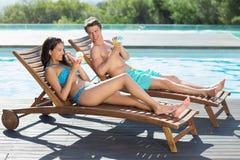 Paarzitting op zonlanterfanters door zwembad Stock Foto