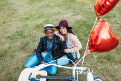 Paarzitting tussen verschillende rassen op een gras met fiets, gitaar en rode ballons Royalty-vrije Stock Foto