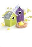 Paasei in een nest met vogelhuizen en berktakken op backgr Stock Foto