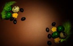 Paaseieren, chocoladedragees, bloemen en veren op bruine bedelaars stock foto's