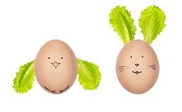 Paaseieren die met verse saladebladeren worden verfraaid Grappige die gezichten op de eieren worden getrokken Paashaas en kip van stock foto