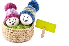 Paaseieren in een mand Emoticons in gebreide hoeden met pom-poms Stock Foto's