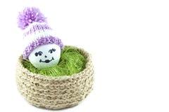 Paaseieren in een mand Emoticons in gebreide hoeden met pom-poms Royalty-vrije Stock Foto