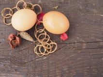 Paaseieren in een mand met decoratie op de lijst stock afbeelding