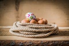 Paaseieren in een mand van kabel wordt gemaakt die Royalty-vrije Stock Foto