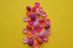 Paaseieren en bloemen van document op een gele achtergrond worden gemaakt die De kleuren zijn roze, Bourgondië, fuchsia en geel D Stock Foto's