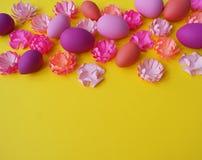 Paaseieren en bloemen van document op een gele achtergrond worden gemaakt die De kleuren zijn roze, Bourgondië, fuchsia en geel D Royalty-vrije Stock Fotografie