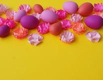 Paaseieren en bloemen van document op een gele achtergrond worden gemaakt die De kleuren zijn roze, Bourgondië, fuchsia en geel D Royalty-vrije Stock Afbeelding