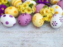 Paaseieren en gele en violette sleutelbloem Stock Fotografie