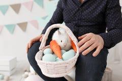 Paaseieren en konijntje in mand op mensenoverlappingen Royalty-vrije Stock Afbeeldingen
