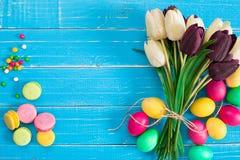 Paaseieren en tulpen op blauwe rustieke houten planken Stock Foto