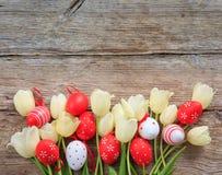 Paaseieren en tulpen op houten ruimte als achtergrond en exemplaar Stock Foto