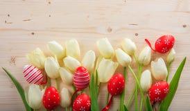 Paaseieren en tulpen op houten ruimte als achtergrond en exemplaar Stock Afbeeldingen