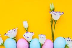 Paaseieren en van de lentebloemen narcissen op gele achtergrond Royalty-vrije Stock Foto's