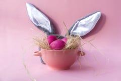 Paaseieren in generische plaat, grijze konijnoren op roze achtergrond royalty-vrije stock fotografie