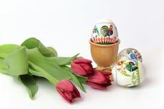 Paaseieren in koppen en rode tulpen Stock Foto