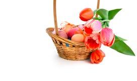 Paaseieren in mand en bos van roze tulpen Stock Foto