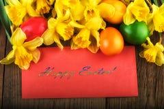 Paaseieren met de lentebloemen op oud hout Tekst Gelukkige Pasen Stock Fotografie