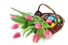 Paaseieren met een mand en een bos van roze tulpen op geïsoleerd w stock foto's