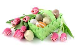 Paaseieren met een mand en een bos van roze tulpen op geïsoleerd w Royalty-vrije Stock Afbeelding