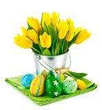 Paaseieren met gele tulpen in emmer stock afbeelding
