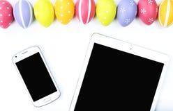 Paaseieren met slimme telefoon en tablet stock afbeeldingen