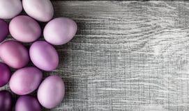 Paaseieren in modieuze kleuren op een grijze houten achtergrond Stock Afbeelding