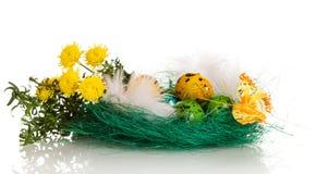 Paaseieren in nest, bloemen, gras en vlinder op wit Stock Afbeelding