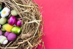 Paaseieren in nest op rood stock afbeelding