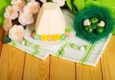 Paaseieren in nest, Pasen-kaasdessert, bloemen, suikergoed en t royalty-vrije stock afbeelding