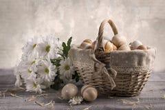 Paaseierenbeige in een mand op een lijst Witte bloemen dichtbij Stock Afbeelding