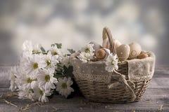 Paaseierenbeige in een mand op een lijst Witte bloemen dichtbij Royalty-vrije Stock Fotografie