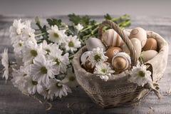 Paaseierenbeige in een mand op een lijst Witte bloemen dichtbij Stock Fotografie