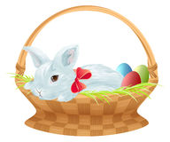 Paashaas in rieten mand Leuke Pasen-konijntjeszitting in mand met kleureneieren Stock Foto