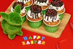 Paashaas van gras en heerlijke heldere cupcakes op een houten raad op een rode achtergrond wordt gemaakt die stock afbeeldingen