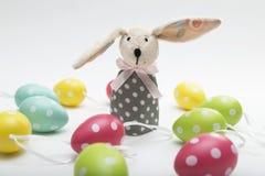 Paashaasstuk speelgoed met het laten vallen van oor die zich dichtbij kleurrijke eieren bevinden stock foto