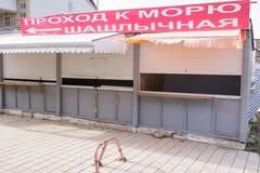Pabellones comerciales cerrados con una bandera, un paso al mar y la barbacoa Fotografía de archivo