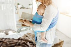 Pacífico el dormir babyboy dulce minúsculo en madre en honda del bebé mientras que mamá hermosa joven que intenta relajar la lect fotografía de archivo
