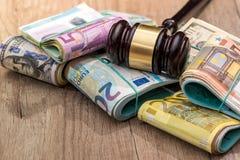 Pacchetti dei dollari, un pacchetto dell'euro con un martello Fotografie Stock Libere da Diritti