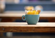 Pacchetti del dolcificante e dello zucchero in una tazza Fotografia Stock