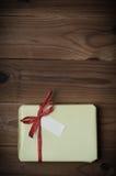 Pacchetto avvolto del regalo con l'arco rosso della rafia su tavolato del legno - Retr Fotografie Stock