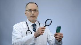 Pacchetto d'esame di medico delle pillole con la lente d'ingrandimento, farmaco falsificato immagini stock libere da diritti