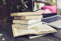 Pacchetto dei libri con il computer portatile sulla tavola di legno Immagine Stock
