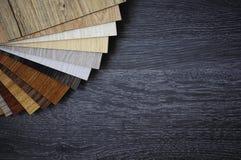 Pacchetto del campione del laminato di legno della pavimentazione sul pavimento nero di legno fotografia stock libera da diritti