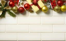 Pacchetto del regalo e decorazioni di Natale sulla parete bianca fotografie stock