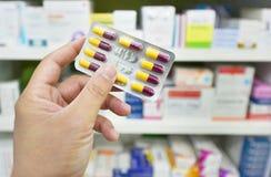 Pacchetto della capsula della medicina della tenuta del farmacista alla farmacia della farmacia Fotografie Stock