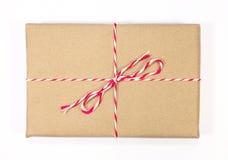 Pacchetto della carta di Brown legato con corda rossa e bianca Fotografie Stock Libere da Diritti