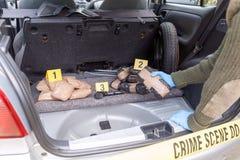 Pacchetto della droga della tenuta dell'ufficiale di polizia scoperto nel tronco di un'automobile fotografie stock libere da diritti