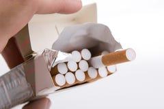Pacchetto delle sigarette in una mano Fotografia Stock Libera da Diritti